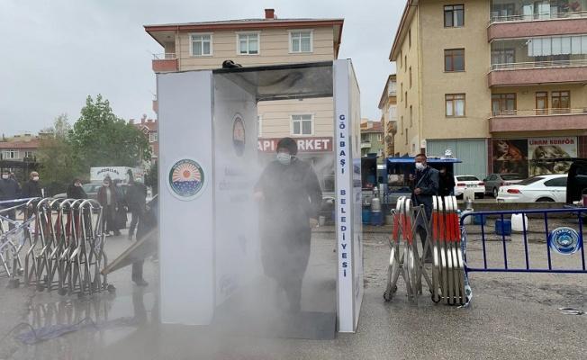 Gölbaşı'nda pazarlara girişler dezenfektan kabininden geçiyor.